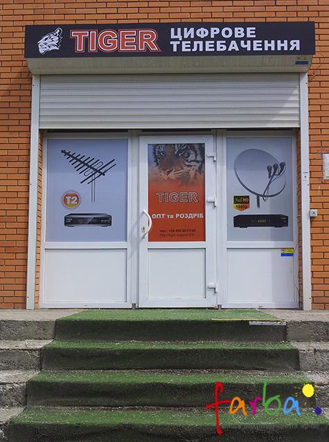 Брендирование входной группы магазина в корпоративный стиль. На окна поклеенная самоклеющаяся пленка с цветной печатью, на которой находится информация для клиентов, сверху находится вывеска с названием заведения.