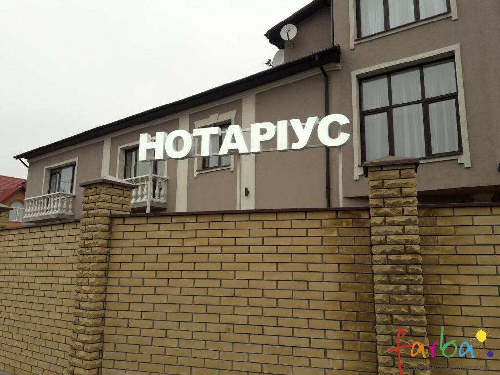 Пластиковые световые объемные буквы, смонтированные на забор дома с помощью металлической рамы.