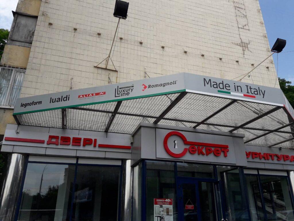 Наружные рекламные вывески, расположенные на фасаде магазина дверей, состоящие из объемных световых букв, расположенных на композитных основаниях, и трех табличек, изготовленных из пластика.