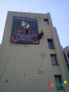 Монтаж промышленными альпинистами конструкции с баннером на стену здания.
