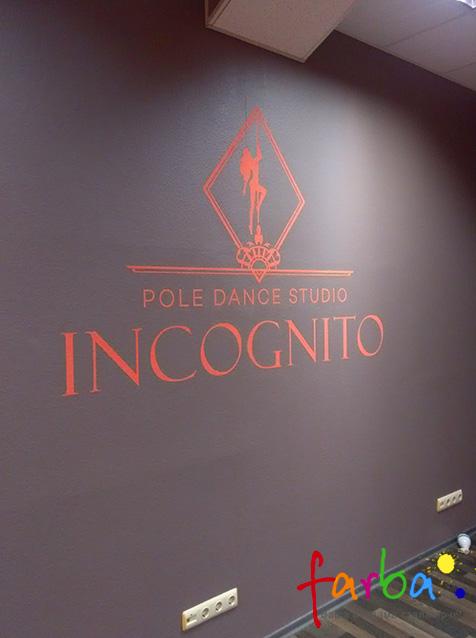 Логотип и название компании, нанесенные на крашеную стену краской другого цвета через одноразовый трафарет с самоклеящейся пленки.