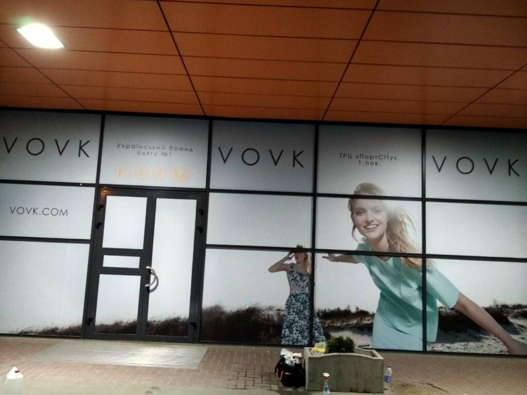 Брендирование входной группы магазина одежды, выполненное в виде оклейки стеклянных частей витрины пленкой с изображением, напечатанным на ней.