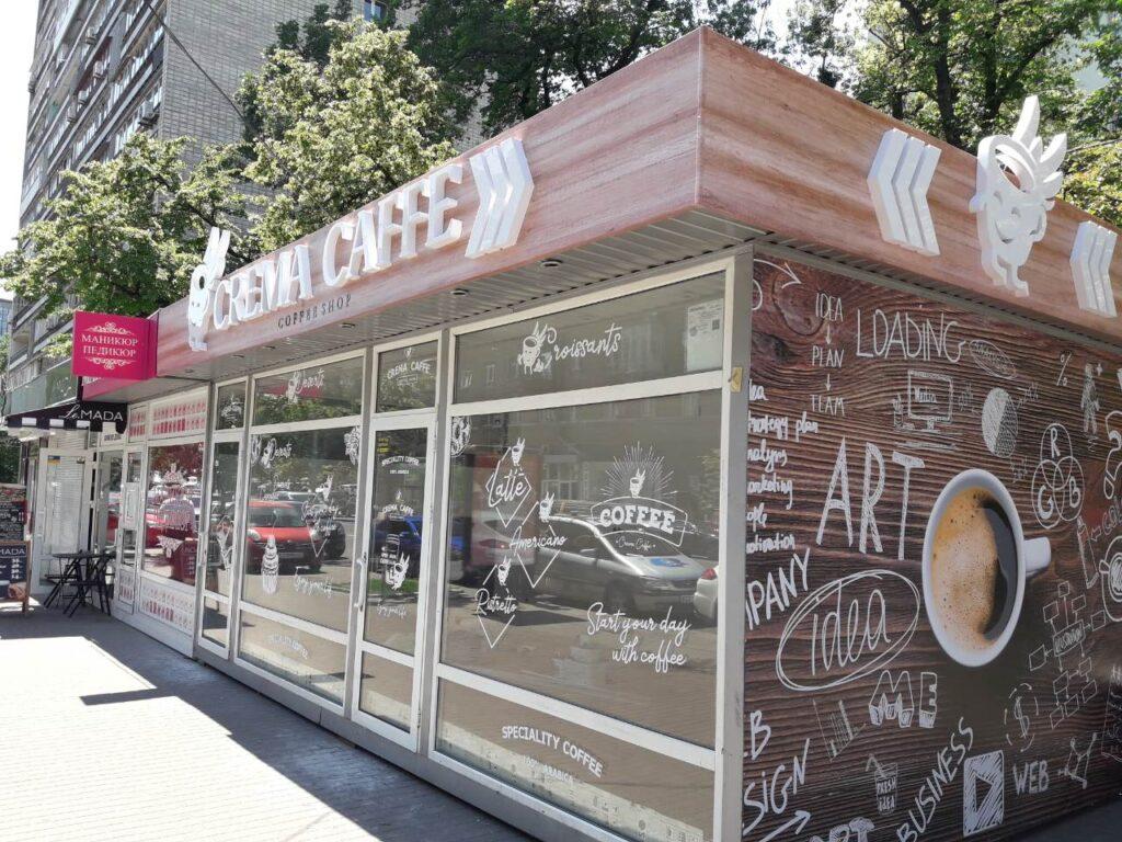 Наружная реклама на киоске по продаже кофе, включающая в себя объемные световые буквы с логотипом, композитный фриз и наклейки на окна. Буквы имеют внутреннюю подсветку, фриз имеет изображение, которое копирует деревянную поверхность, наклейки изготовлены из белой пленки и нанесены на стекло.