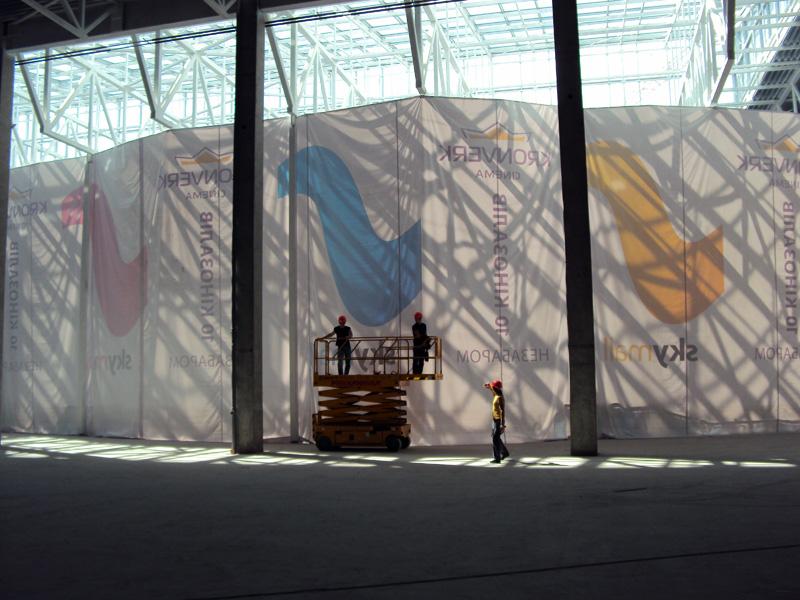 Монтаж завесы из баннеров для зонирования пространства в торговом центре. Для данного вида монтажа используется подъемная техника.