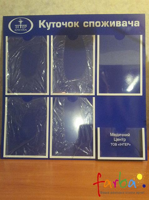 Уголок потребителя в виде пластикового стенда с пятью карманами для листов формата А4 и одним для книги жалоб и предложений.