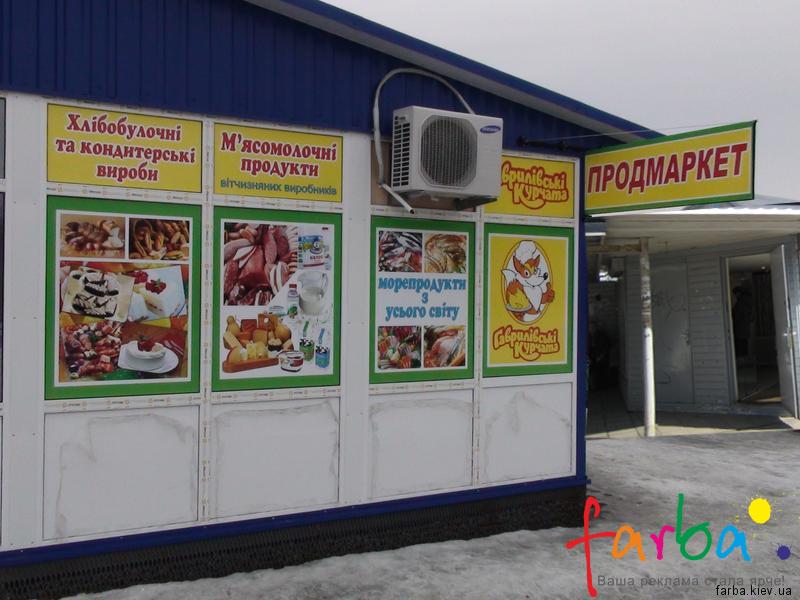 Реклама на фасаде магазина продуктовых товаров, выполнена с использованием цветных наклеек на окна и выносной двусторонней вывески с металлической рамкой.