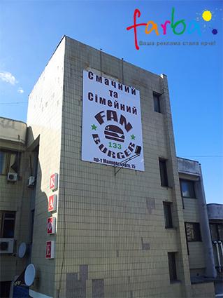 Брендмауэр изготовили и закрепили на стене дома с помощью автовышки. Размер 5х8 метров, напечатанный на литой баннерной ткани.