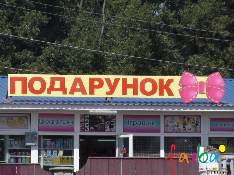 Вывеска из пластика, изготовленная путем нанесения полноцветной печати, закрепленная на крыше магазина на металлические кронштейны.