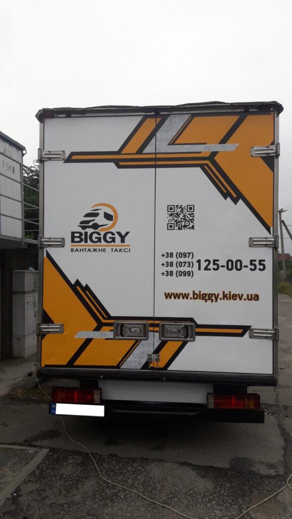 Задние двери будки грузового автомобиля, на которые нанесена самоклеющаяся пленка с рекламой.