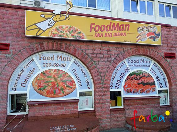 Оформление фасада магазина по доставке еды. На окна нанесены наклейки с тематическими изображениями и, нужной для клиентов, информацией, сверху прикреплен световой короб с элементами, которые вынесены за пределы основания.