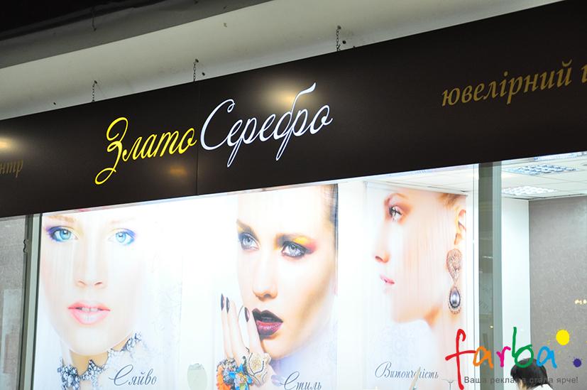 Композитный короб со световыми буквами посередине, закрепленный над входом в магазин на декоративные цепи.