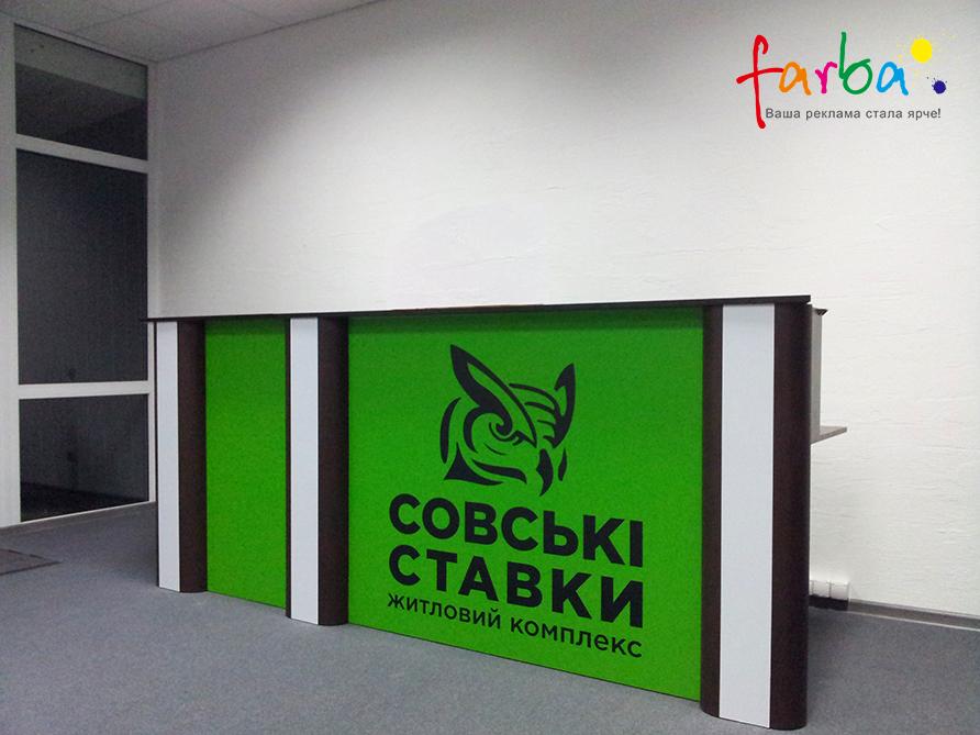 Наклейка черного цвета, изготовленная с помощью плоттерной резки и поклеенная на плоскость зеленого цвета внутри помещения.